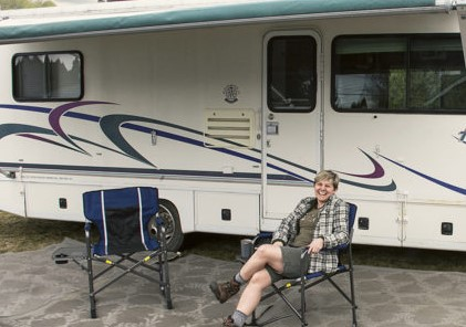 person sitting in chair in front of an RV